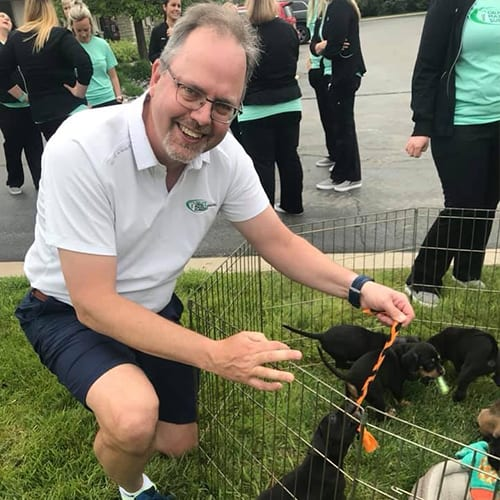 Dr. Poupard Playing With Puppies