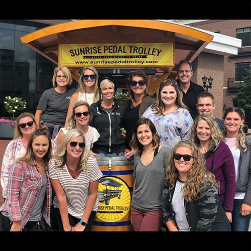 Staff Posing In Front of Sunrise Pedal Trolley Sign